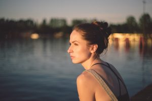 young woman thoughtfully staring over lake